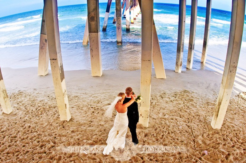 Wedding Picture Of A Couple Under Pier At Wrightsville Beach Looking Out To The Atlantic