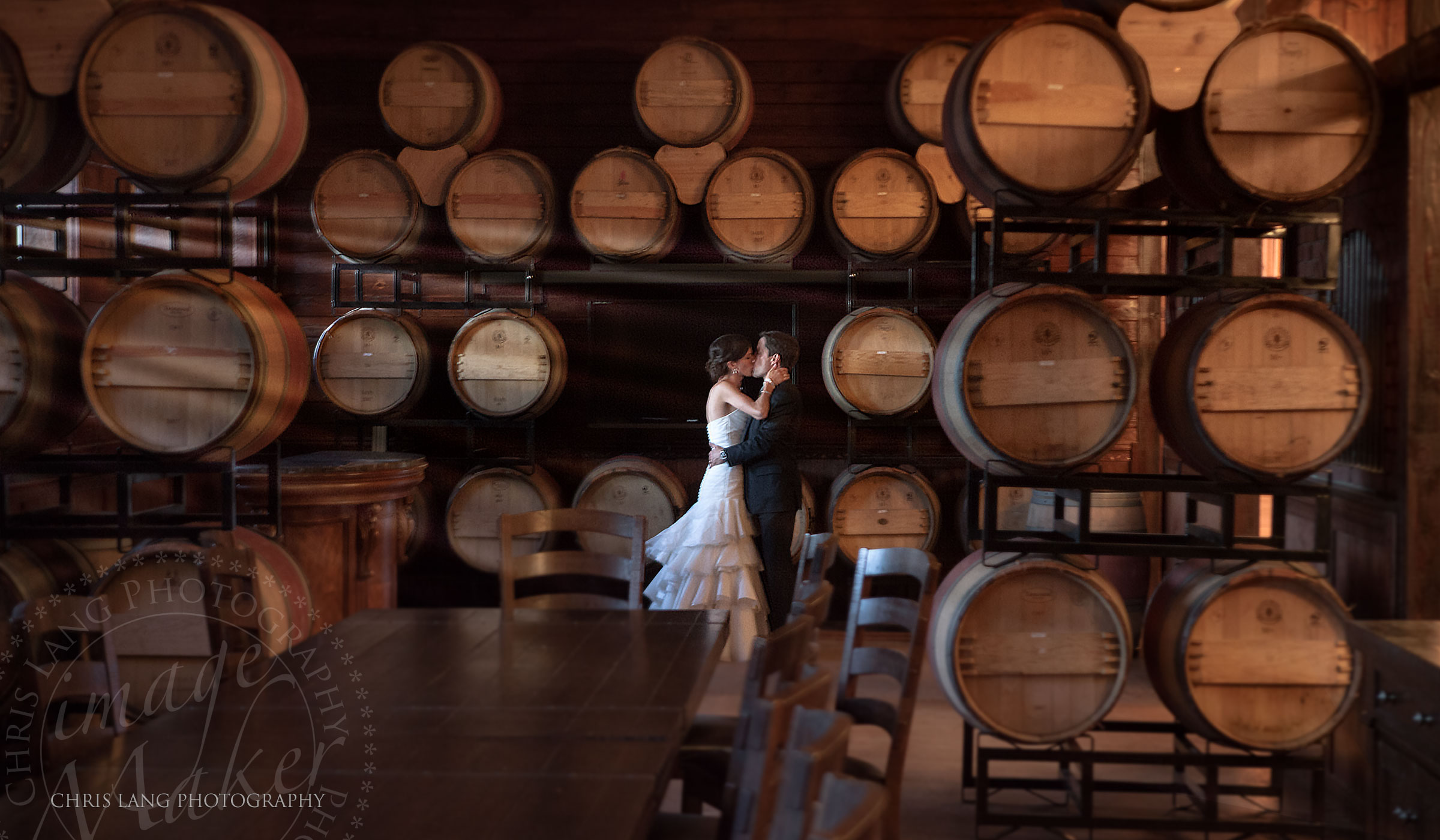 Bride and groom kissingi in a winery inbetween wine barrels - Wedding Photograpy Ideas -lWIlmington NC Wedding Photographers -