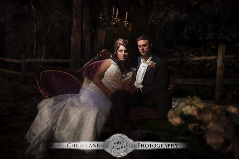 A Romantic Wedding Picture Of Newlyweds On Counch Outside At Night Lit By Chandelier